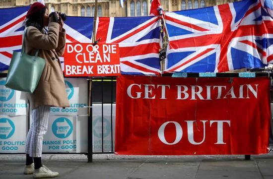"""10月28日,在英国伦敦议会大厦外,一名女子站在英国国旗和支持英国""""脱欧""""的标语旁拍照。新华社/路透"""