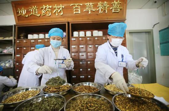 2020年3月5日,在江苏省南通市,南通汉药中医医院的医务人员在称量中药预防茶饮剂的药材。徐培钦 / for China Daily