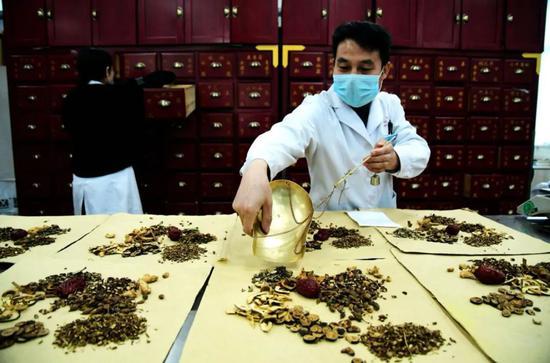 2020年2月17日,山东青岛西海岸新区中医医院,一位中药师在给患者分装中成药剂。俞方平/ for China Daily