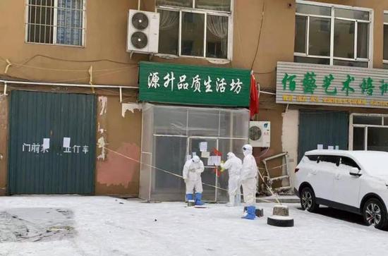 在通化市源升品质养生坊门外,几名疾控部门工作人员正在工作。图片据新华社