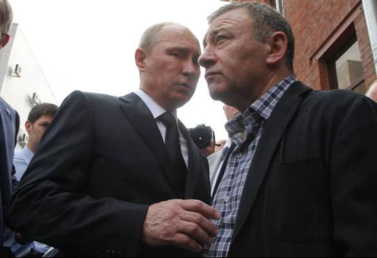 (图说:2013年8月9日,普京和罗滕贝格在圣彼得堡出席柔道教练拉赫林的葬礼。图/Getty Images)