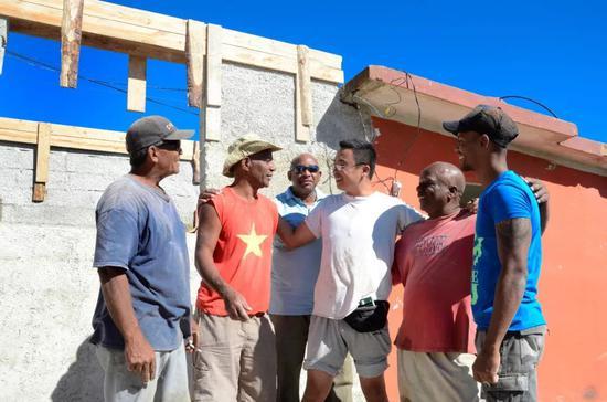 2月6日,那伟建(右三)在古巴首都哈瓦那雷格拉区和当地受灾居民聊天。新华社发(华金·埃尔南德斯摄)