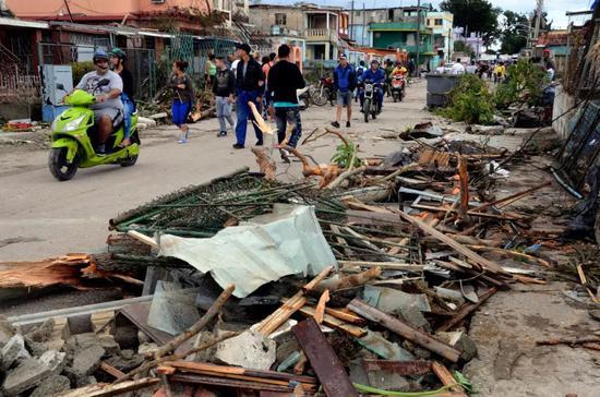 在古巴首都哈瓦那雷格拉区,人们从因龙卷风和暴雨受损的房屋旁走过。 新华社发(华金·埃尔南德斯摄)