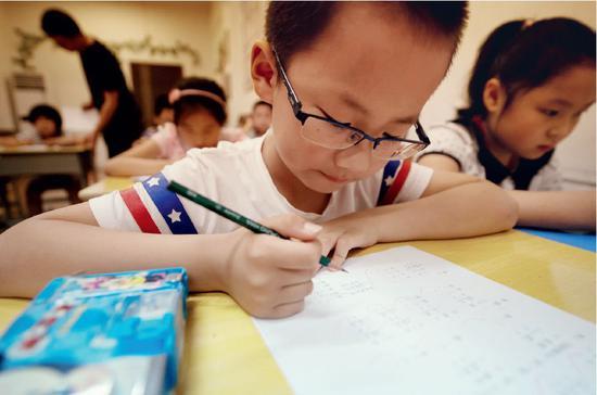 在暑期奥数补习班上解题的二年级小学生。图/新华