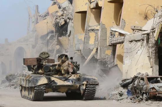 """2016年10月14日,在利比亚西部城市苏尔特,利比亚民族团结政府卫队成员参与打击极端组织""""伊斯兰国""""的军事行动。(新华社/法新)"""