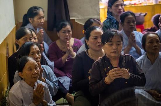"""28日,越南河静省,疑为""""死亡货车""""遇难者的范氏茶眉的家人和邻居为她祷告。"""