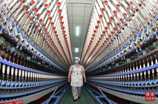 △2020年5月6日,在新疆维吾尔自治区巴音郭楞蒙古自治州库尔勒经济技术开发区某棉纺公司,正在进行生产工序作业。中新社发 确·胡热 摄