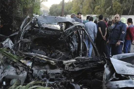 """4月6日,在叙利亚大马士革,当地居民聚集在一辆被""""伊斯兰军""""炸毁的汽车旁。新华社/美联"""