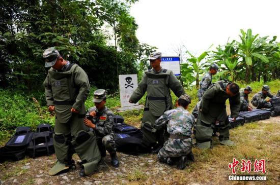 资料图:排雷官兵相互协作穿戴防护装具。安源 摄