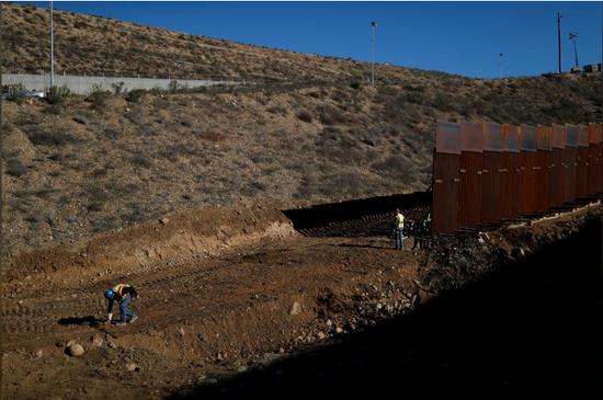 美国工人在修筑墨西哥和美国的边境墙时,在地上画了一条线。(路透社)