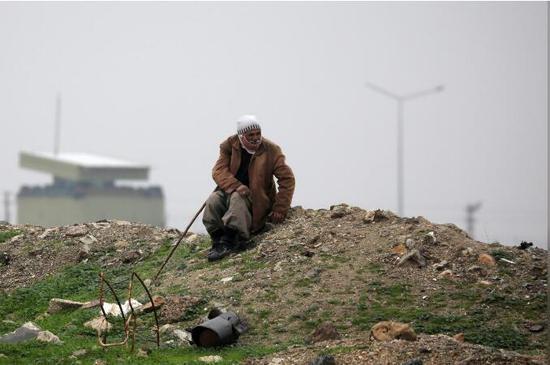 12月20日,土叙边境叙利亚一侧的一位长者在息憩,他周围满是搏斗的创伤。(图:路透)