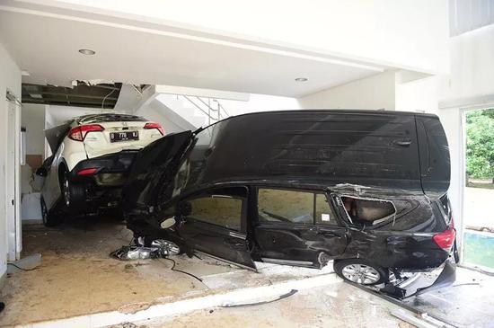 这是12月25日在印尼万丹省丹戎勒松度伪村拍摄的被海啸冲入房屋的车辆。(新华社记者杜宇摄)