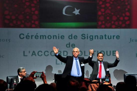 2015年12月17日,在摩洛哥斯希拉特,利比亚两个对立议会的代表在利比亚最终和平协议签署仪式上举手致意。(新华社记者 张远 摄)