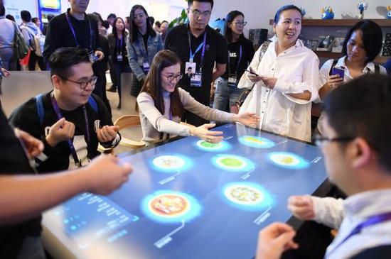 """资料图:观众在2017杭州·云栖大会的蚂蚁金服展厅体验""""未来餐厅""""的自助点餐服务。"""