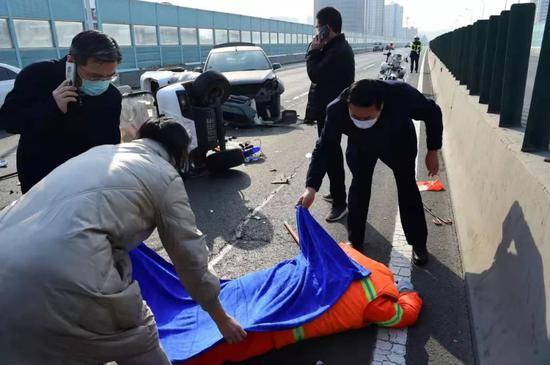 邓沛然为受伤环卫工人盖上毛毯。张晓峰摄