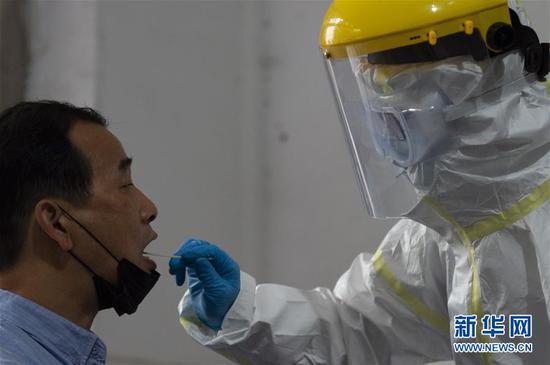 在湖北省襄阳市樊城区检测点,工作人员给一位教师采集咽拭子(4月18日摄)。新华社发(谢剑飞 摄)