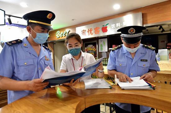 红桥市场地下食美汇美食广场,东城市场监管局执法人员检查每日消毒记录。