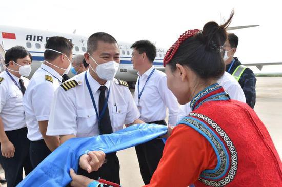 乌兰牧骑艺术家向机组献上圣洁的哈达。吕俊杰摄