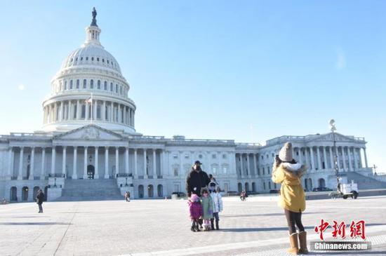 当地时间12月29日,美国首都华盛顿,民众佩戴口罩拍照。