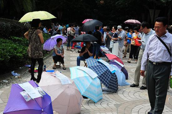 2014年9月27日,上海人民公园相亲角内人头攒动,父母将子女的征婚信息贴在雨伞上。