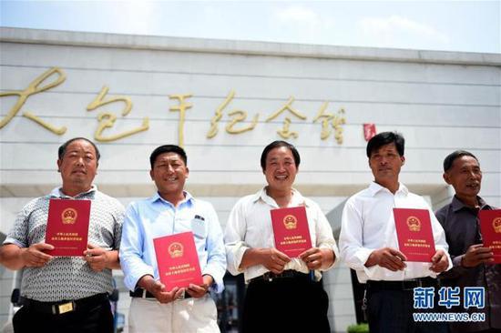 小岗村农民展示领到的《农村土地承包经营权证》(2015年7月8日摄)。 新华社记者刘军喜摄