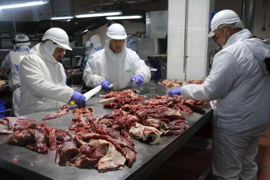 在布宜诺斯艾利斯西北300多公里的休斯镇,黑竹牛肉加工厂的工人在处理牛肉。(新华社记者倪瑞捷摄)