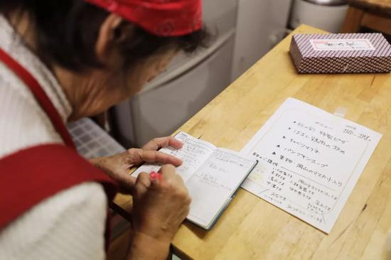 老奶奶抄写当天菜单内容。菜单上标有当日每道菜品和施舍食材的小我、企业名字。