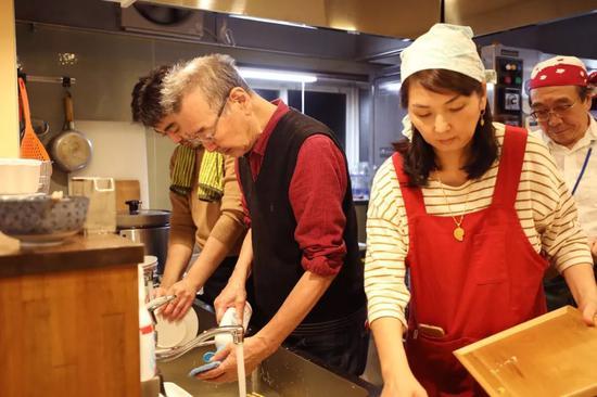 岩田(右二)和山田(左二)清洗清理餐具。