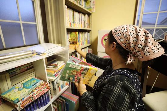 自愿者在朝霞儿童食堂二楼的房间里清理捐来的图书。