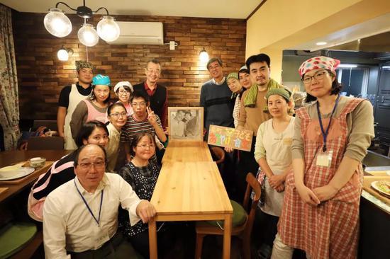 在朝霞儿童食堂,当天来做事的自愿者与山田相符影留念。中间桌上摆着山田和妻子的相符照。