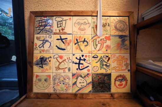"""早霞儿童食堂门口摆着孩子们做的手工艺品,上有山田的头像和""""要町早霞儿童食堂""""字样。"""