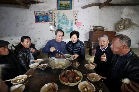 许家印夫妇和同乡们在堂屋吃忆苦思甜饭
