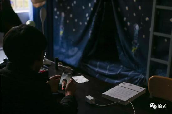 △2018年12月19日,禄劝一中,高三文科培优班的李维国坐在寝室里给她妈妈打视频电话。
