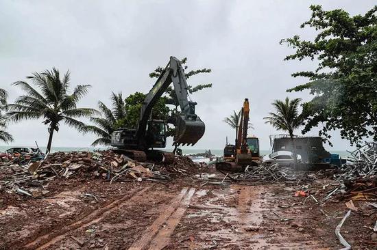 12月25日,声援人员在印尼万丹省清算遭海啸损坏的修建。(新华社记者张可任摄)