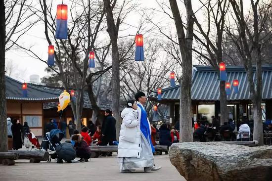 2月5日,一对年轻情侣身着韩服在韩国京畿道龙仁市的韩国民俗村参观。当日是农历新年第一天,不少韩国民众身着韩服来到韩国民俗村体验年俗。韩国民俗村有传统住宅260余座,再现了朝鲜半岛传统社会的风貌。在节假日期间安排丰富多彩的民俗游戏,供游客体验。新华社记者 王婧嫱摄
