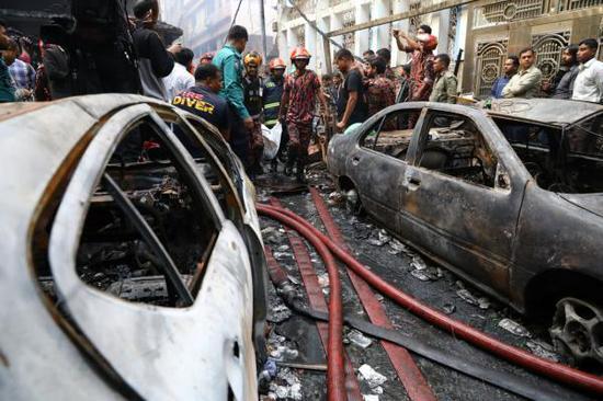 2月21日,在孟加拉国达卡,工作人员在火灾现场转移遇难者遗体。 新华社 图