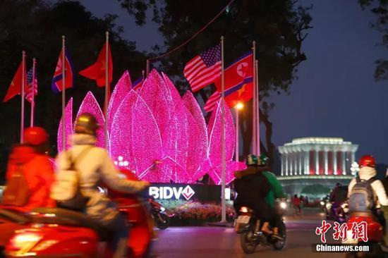 """当地时间2月25日,胡志明主席纪念堂附近形似越南""""国花""""金莲花的花灯亮起灯光,美、朝、越三国国旗围绕花灯形成圆形。中新社记者富田 摄"""