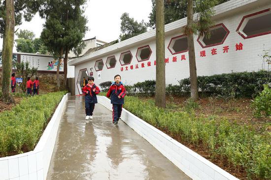 ↑贵州省织金县金龙小学的学生走过新建的冲水卫生厕所(2018年10月23日摄)。新华社记者 张玉薇 摄