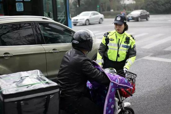 钟萍拦下一辆违法走机动车道的电动车,进行安全教育 本报记者 吴崇远 /摄