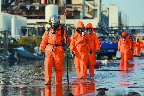 3月23日下午,江苏盐城市响水县,天嘉宜化工有限公司爆炸后的现场,全副武装的救援人员穿越废水进行作业 。图/视觉中国