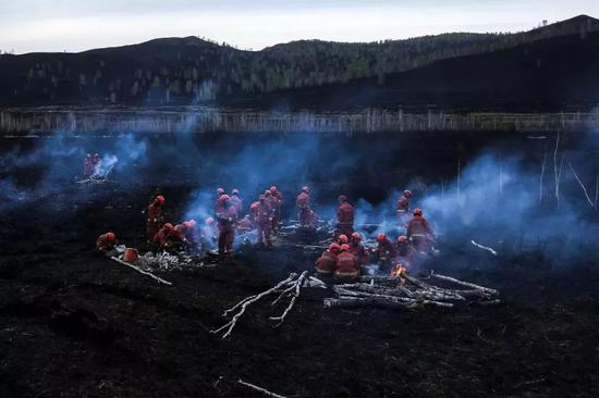 △2017年5月20日,内蒙古大兴安岭,扑火后的消防员在火烧迹地内休息。