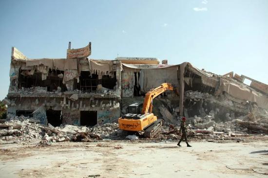 2011年10月30日,在利比亚首都的黎波里,挖掘机在拆除象征卡扎菲权力的阿齐齐亚兵营。(新华社发 哈姆扎·图尔基亚摄)