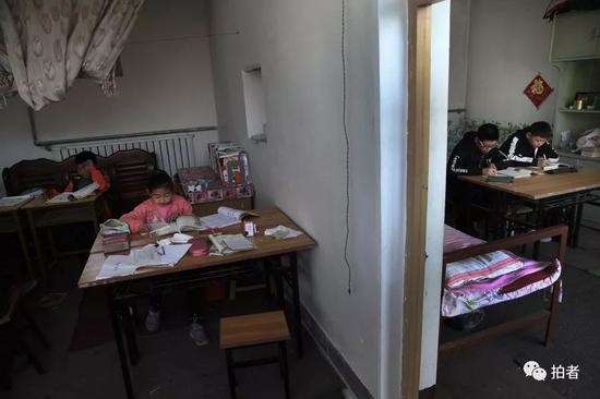 """4月5日,河北涞水西官庄村,""""小课桌""""上,一面墙隔开了""""小学部""""和""""中学部""""。新京报记者尹亚飞摄"""
