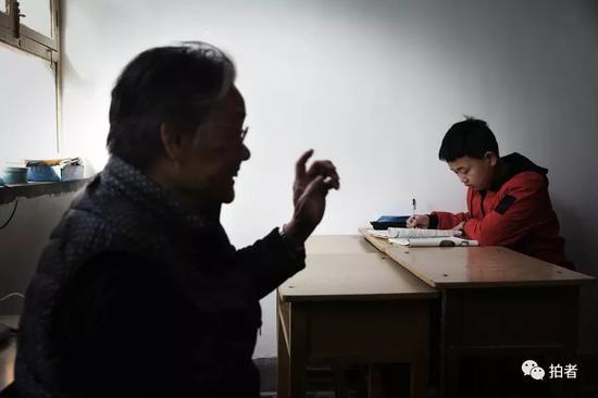"""4月5日,河北涞水西官庄村,""""小课桌""""上,严敏文正在跟孩子交流。新京报记者尹亚飞摄"""