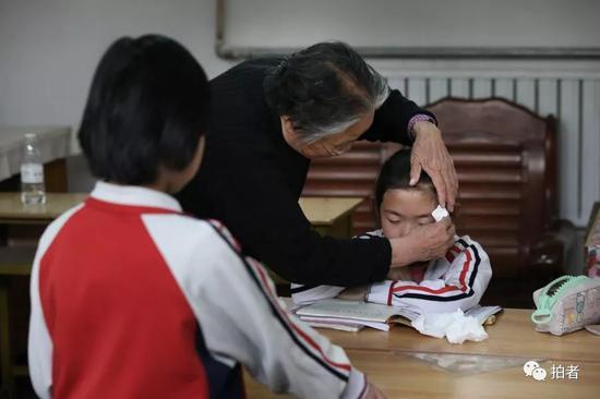 严敏文看到后,立即过去安慰她,并用手中的纸巾拭去小女孩儿的泪水。新京报记者尹亚飞摄