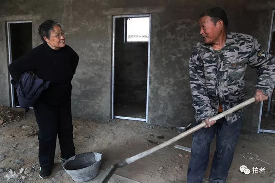 在新教室工地上,严敏文正在向工人了解工程进度。新京报记者尹亚飞摄