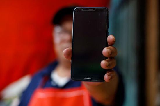 餐馆员工展示他的华为手机。新华社发