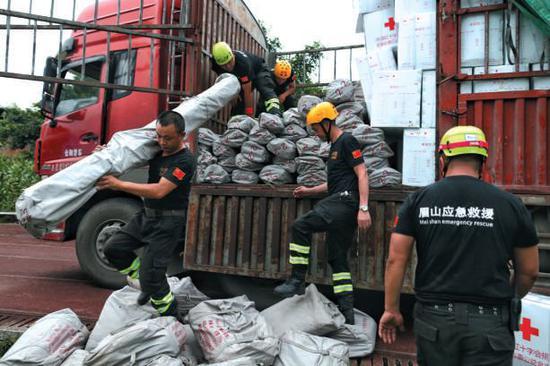 ▲昨日,救援人员从货车上搬下帐篷支架,准备向安置点增援。新京报记者 彭子洋 摄