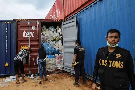 6月15日,印尼环保局海关官员检查装满塑料垃圾的集装箱。/视觉中国