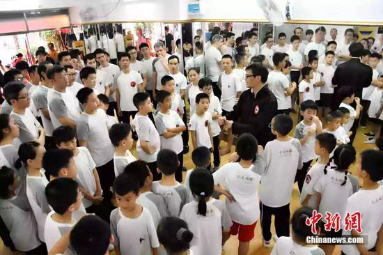 袁师傅的弟子涵盖了各个年龄段,年纪最大的今年65岁,还有很多正在上小学小朋友。还吸引了不少外国人学习咏春。图为袁师傅和弟子在拳馆。受访者供图